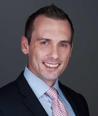 smiling man wearing black suite light blue shirt and polka dot pink tie